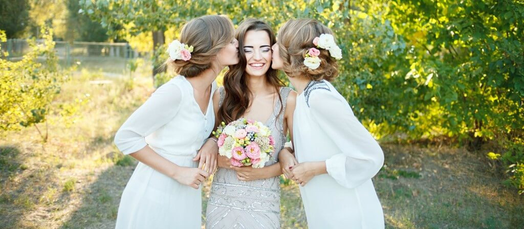A bride being kissed on the cheek by two bridesmaids on either side of her